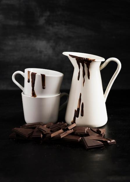Recipientes brancos cheios de chocolate derretido e pedaços de chocolate Foto gratuita
