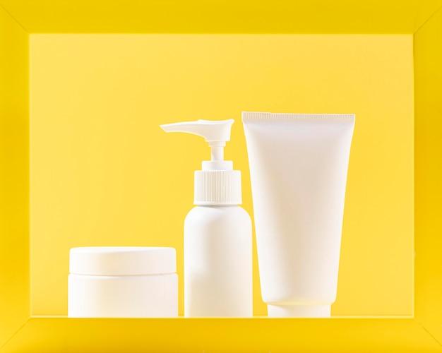 Recipientes cosméticos com fundo amarelo Foto gratuita