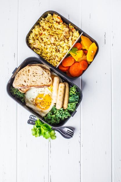Recipientes da preparação da refeição com arroz com galinha, vegetais cozidos, ovos, salsichas e tiro aéreo da salada. Foto Premium