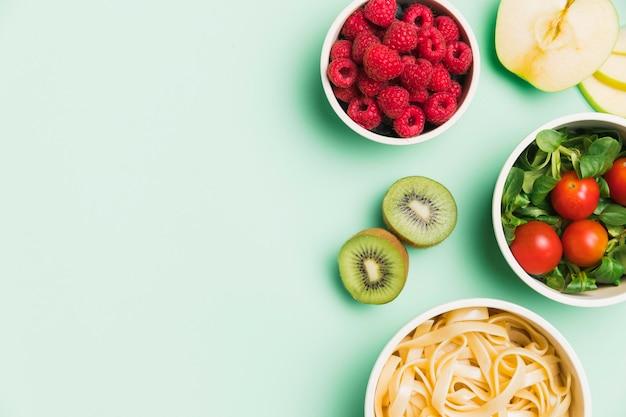 Recipientes de comida de vista superior com framboesas, salada e macarrão com cópia-espaço Foto Premium