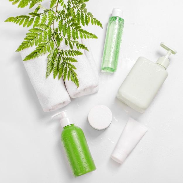Recipientes de cosméticos com folhas verdes de ervas e gotas de água, pacote de rótulo em branco para a marca de mock-up. creme hidratante, shampoo, tônico, cuidados com a pele do rosto e do corpo. Foto Premium