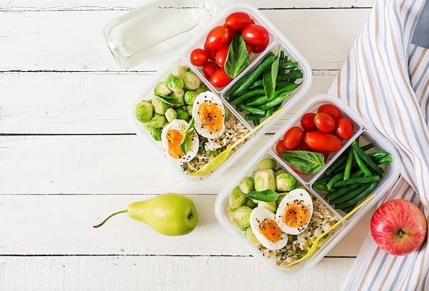 Recipientes de preparação de refeição vegetariana com ovos, couve de bruxelas, feijão verde e tomate. jantar na lancheira. vista do topo. configuração plana Foto gratuita
