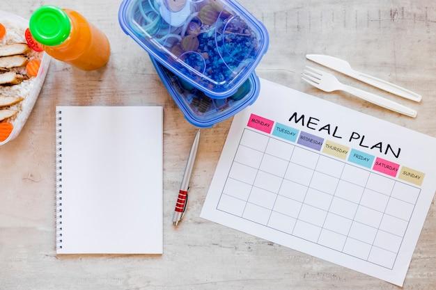 Recipientes de refeição plana leigos com notebook Foto gratuita