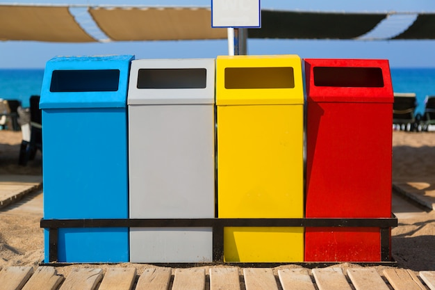Recipientes de tanques de cores diferentes para coleta seletiva de resíduos e lixo na praia do mar. Foto Premium