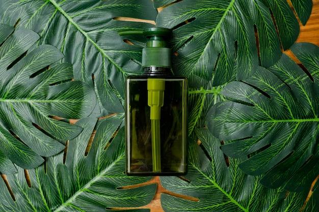 Recipientes naturais da garrafa dos cosméticos no fundo verde da folha, garrafa vazia, produto natural do skincare da beleza, Foto Premium
