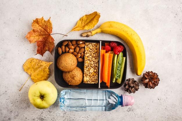Recipientes saudáveis da preparação da refeição à escola com barra, frutas, vegetais e petiscos do cereal. alimento afastado no fundo branco, vista superior. Foto Premium