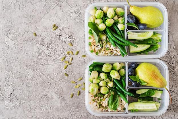 Recipientes veganos de preparação de refeições verdes com arroz, feijão verde, couve de bruxelas, pepino e frutas. jantar na lancheira. Foto gratuita