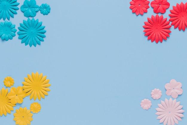 Recorte de flor decorativa colorida no canto do fundo azul Foto gratuita