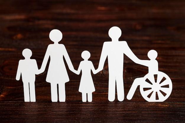 Recorte de papel de diferentes membros da família em fundo de madeira Foto gratuita