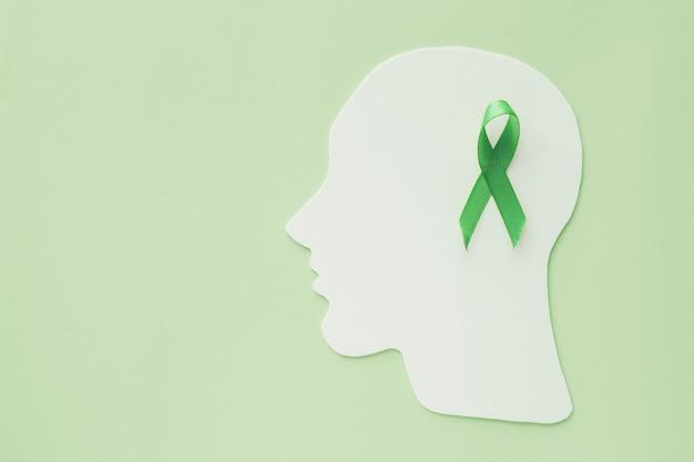 Recorte de papel do cérebro com fita verde sobre fundo verde, conceito de saúde mental, dia mundial da saúde mental Foto Premium