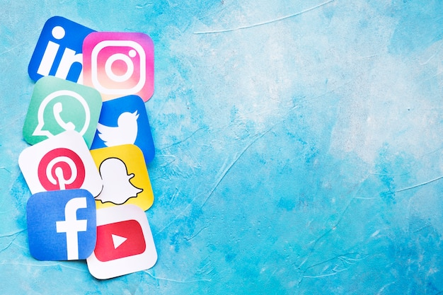 Recortes de papel de ícones de redes sociais sobre o pano de fundo azul Foto gratuita