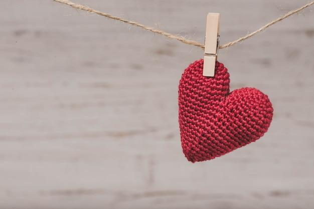 Red pelúcia coração pendurado em uma corda Foto gratuita