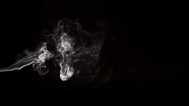 Redemoinhos de fumo branco abstrato sobre o fundo preto Foto gratuita