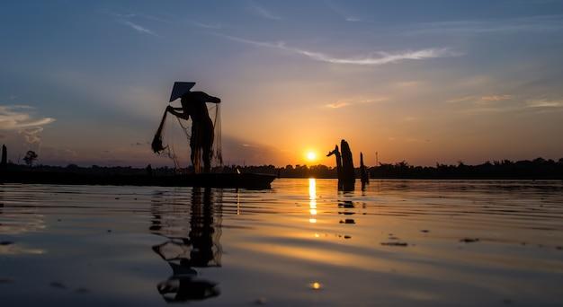 Redes de pesca do pescador da silhueta no barco. Foto Premium
