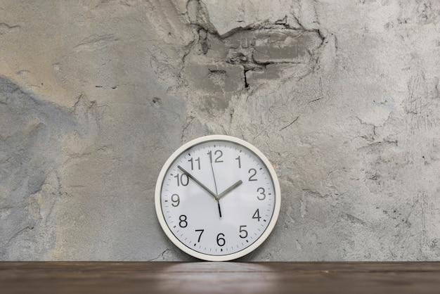 Redondo, face relógio, inclinar-se, contra, danificado, parede concreta, ligado, escrivaninha madeira Foto gratuita