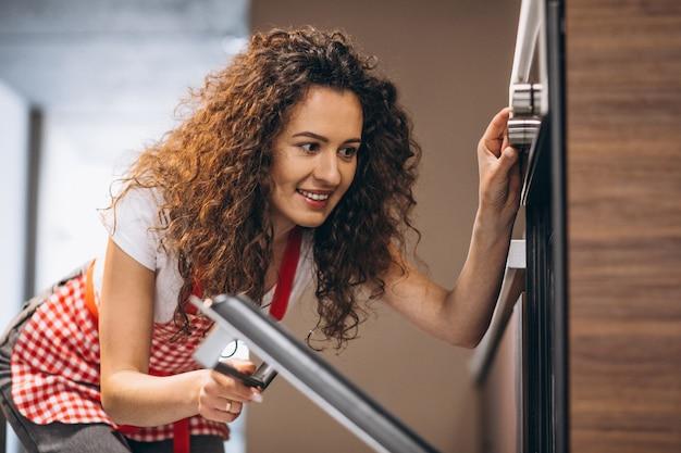 Refeição de cozimento de mulher no forno Foto gratuita