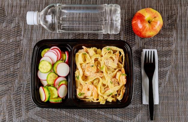 Refeição pronta no recipiente de alimento com água e maçã. Foto Premium