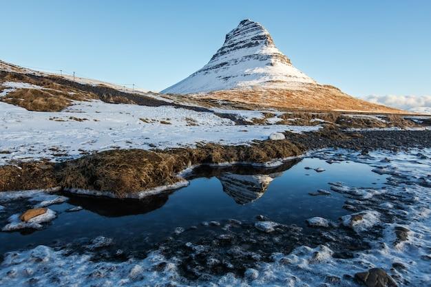 Reflexão da montanha kirkjufell sob céu claro durante a manhã de inverno Foto Premium