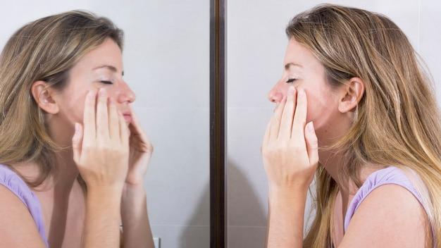 Reflexão, de, mulher, em, a, espelho, lavando, dela, rosto Foto gratuita