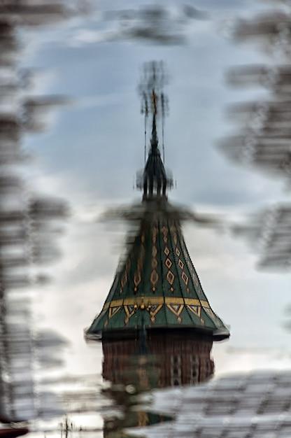 Reflexão de uma torre de igreja em uma poça na rua Foto Premium