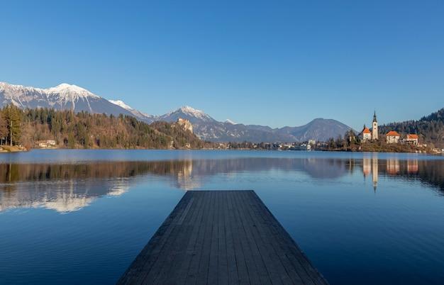 Reflexo das montanhas e edifícios antigos no lago com um píer de madeira em primeiro plano Foto gratuita