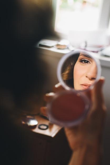 Reflexo do rosto de mulher bonita no espelho em seus braços Foto gratuita