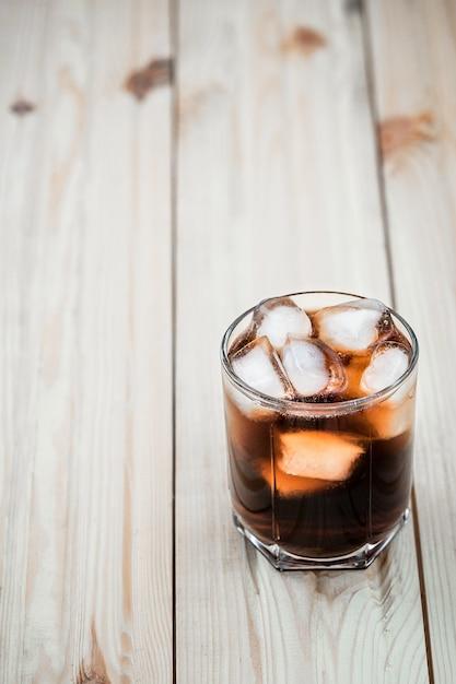 Refrigerantes. copo de cola com cubos de gelo em uma mesa de madeira Foto Premium