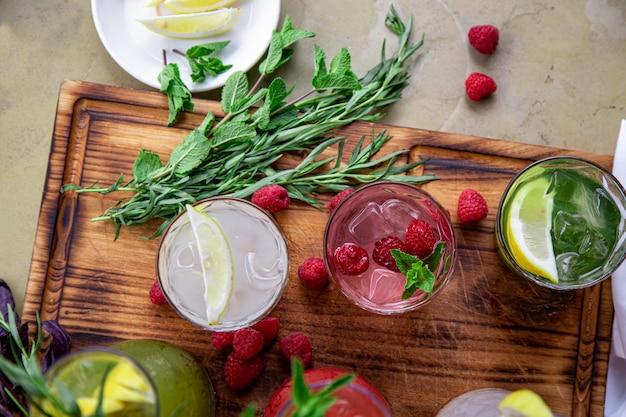 Refrigerantes de verão, um conjunto de limonadas. limonadas em jarras sobre a mesa, cujos ingredientes são feitos, estão dispostos ao redor. Foto Premium