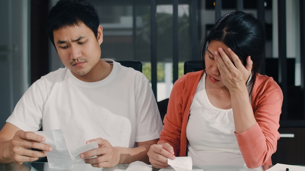 Registros asiáticos grávidos novos dos pares das receitas e despesas em casa. mãe preocupada, séria, estresse enquanto registra orçamento, imposto, documento financeiro, trabalhando na sala de estar em casa. Foto gratuita