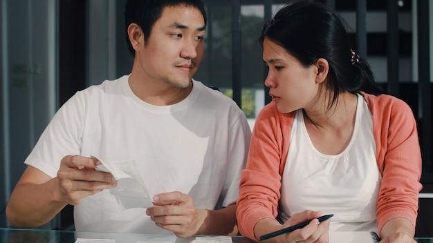 Registros asiáticos grávidos novos dos pares das receitas e despesas em casa. mamãe e papai felizes usando o orçamento recorde de laptop, impostos, documento financeiro, comércio eletrônico, trabalhando na sala de estar em casa. Foto gratuita