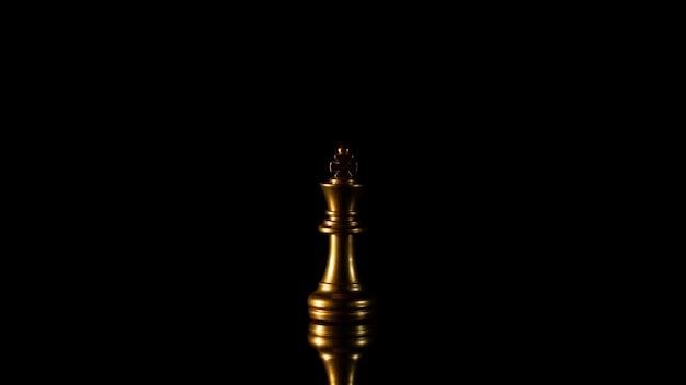 Rei de xadrez de ouro solitário em pé no escuro. Foto Premium