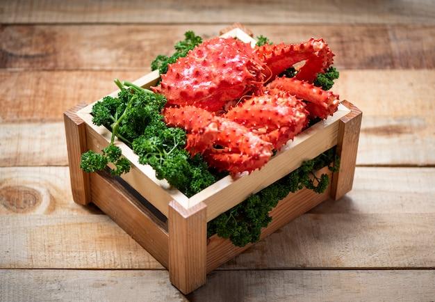 Rei do alasca caranguejo cozido vapor ou marisco cozido em salsa verde encaracolado em caixa de madeira com madeira - hokkaido caranguejo vermelho fresco Foto Premium