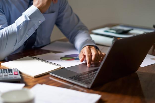 Relatório de contabilidade de verificação de trabalho do homem de negócio no portátil no escritório. Foto Premium