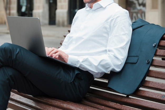 Relaxado, homem negócios, sentar-se banco, usando computador portátil Foto gratuita