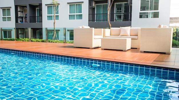 Relaxante cadeiras de vime com travesseiros ao lado da piscina Foto Premium