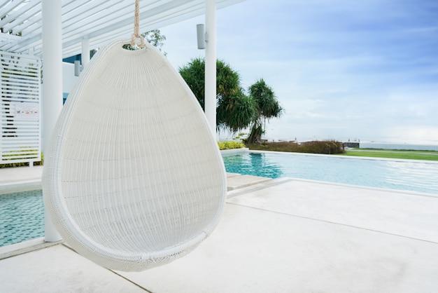 Relaxante rattan branco pendurado cadeira na piscina na vista para o mar Foto Premium
