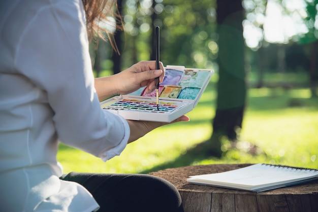 Relaxe a mulher pintando o trabalho de arte em aquarela na natureza da floresta de jardim verde Foto gratuita