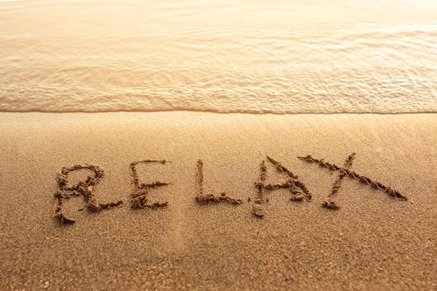 Relaxe escrito na areia Foto gratuita