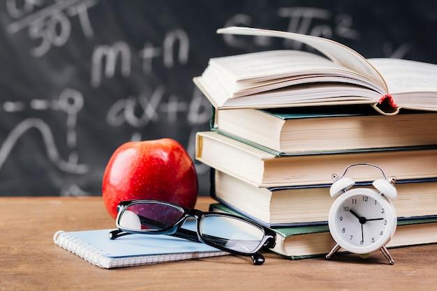 Relógio à frente dos livros didáticos na mesa do professor Foto gratuita