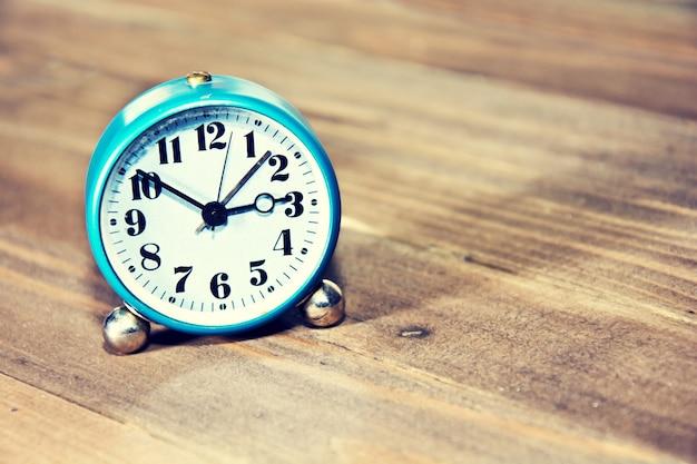 Relógio antigo no fundo de madeira. Foto gratuita