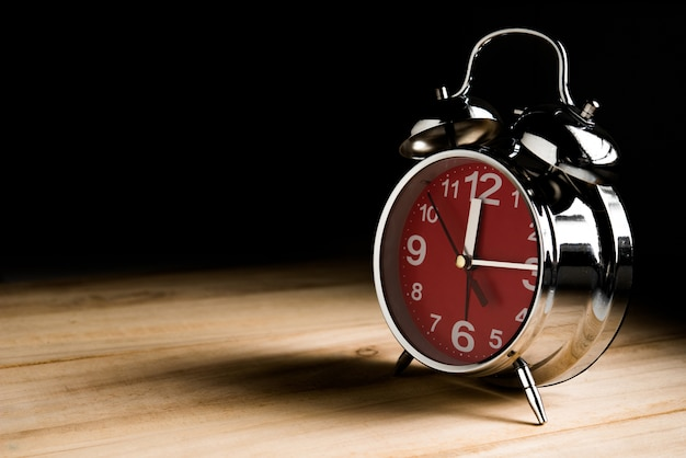 Relógio às 12 horas na mesa de madeira em tom escuro com fundo preto Foto Premium