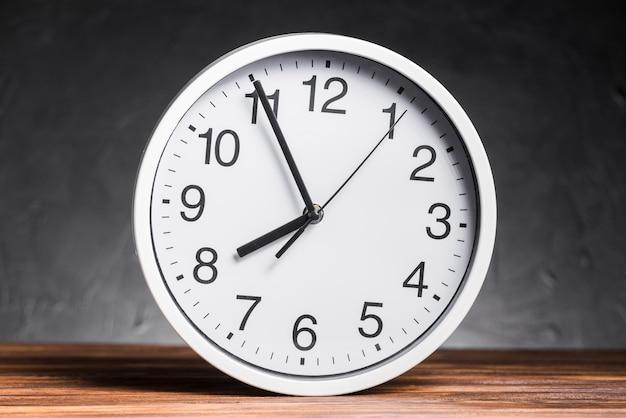 Relógio branco na mesa de madeira contra o fundo preto Foto gratuita