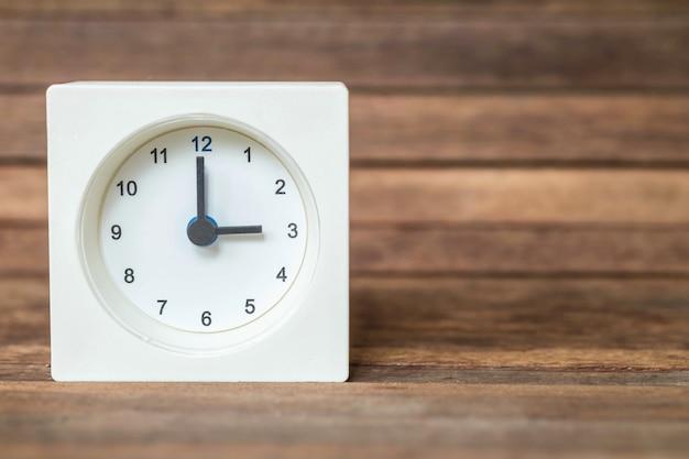 Relógio branco no fundo da placa de madeira marrom turva Foto Premium