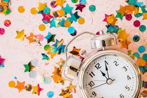 Relógio com lantejoulas brilhantes na mesa Foto gratuita