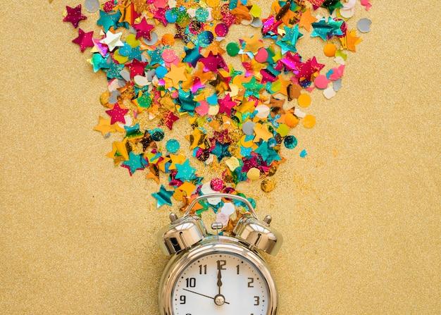 Relógio com lantejoulas na mesa Foto gratuita