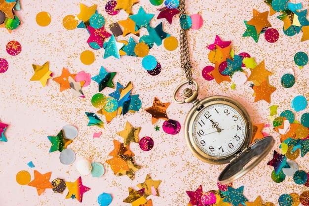 Relógio de bolso com lantejoulas na mesa Foto gratuita
