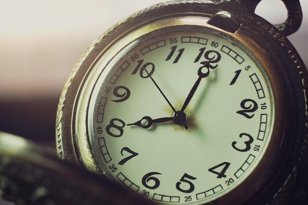 Relógio de bolso do close up na tabela e na luz solar. às 8 da manhã. horas da manhã. conceito de começar o trabalho hoje. Foto Premium