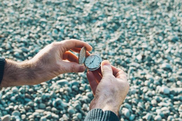 Relógio de bolso nas mãos dos homens. pele de vitiligo. hora da terra. fundo de seixos. Foto Premium
