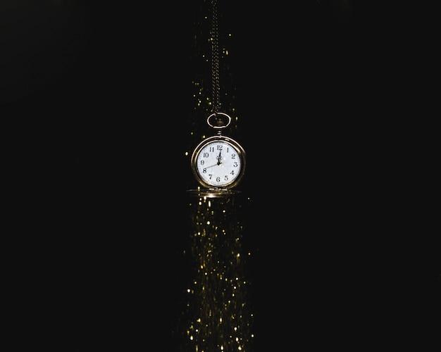 Relógio de bolso pendurado sob lantejoulas caindo Foto gratuita