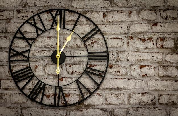 Relógio de ferro vintage na parede de tijolos com mãos de ouro Foto Premium